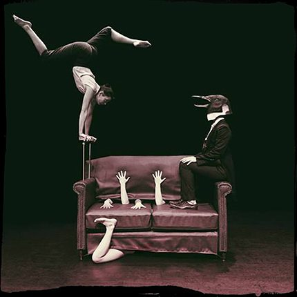 Bird headed man in evening dress sits on a sofa, hands and arms appear through the leather cover and a trapeze artist balances from one arm