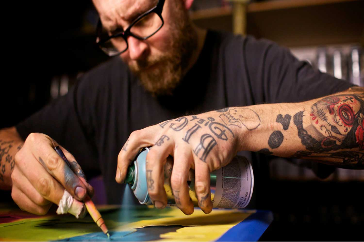 a man in glasses spraying colour on paper