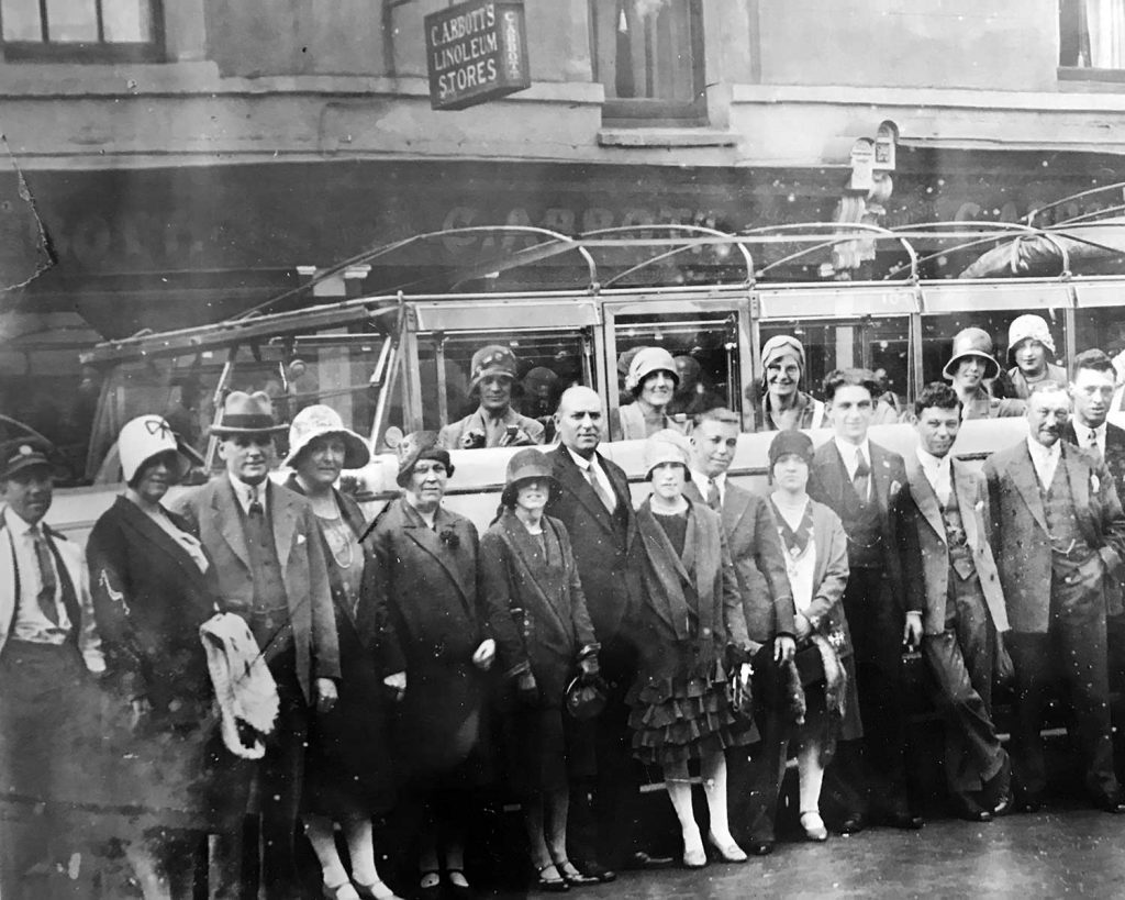 people standing in the front of a car, black and white