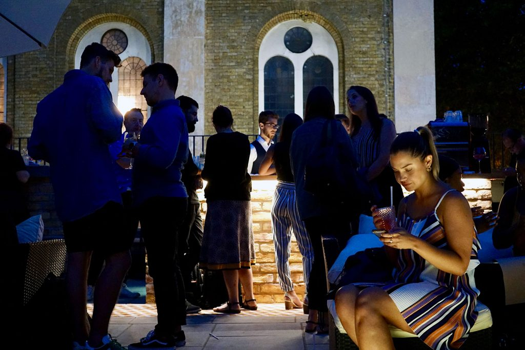 Atmospheric shot of people drinking on roof terrace at Chringuito in Bethnal Green