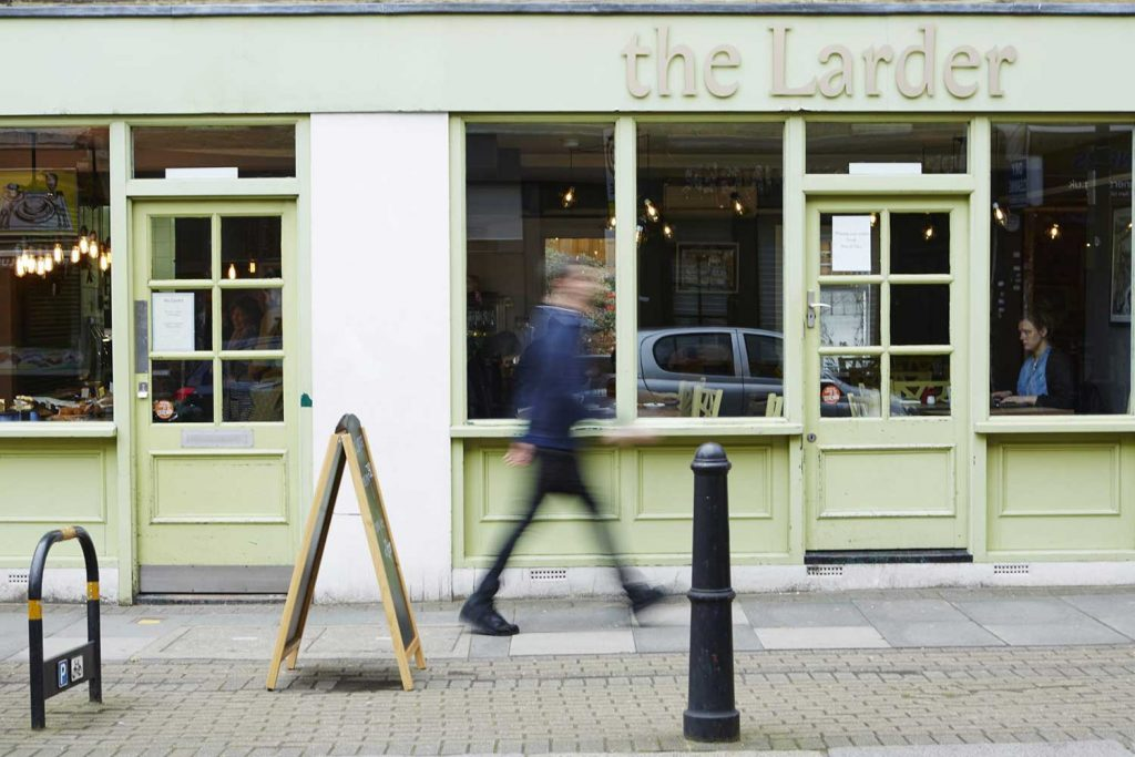 Green shopfront of The Larder vegan cafe on Globe Road, East London