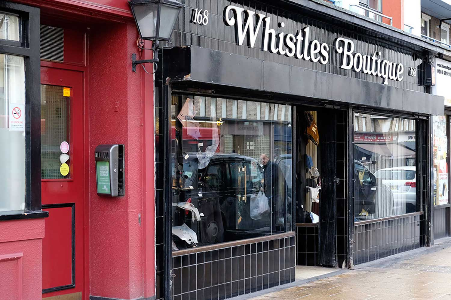 Black shopfront with fifties font of Whistles Boutique on Roman Road, Globe Town, East London