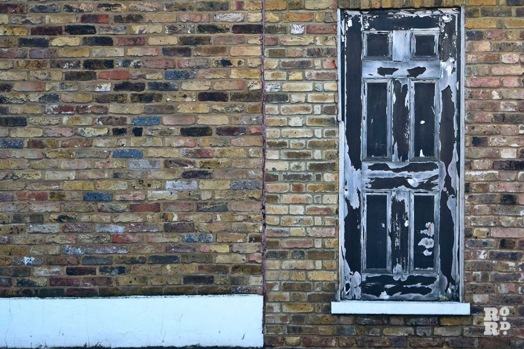 Peeling black painted door in London brick wall in Bow