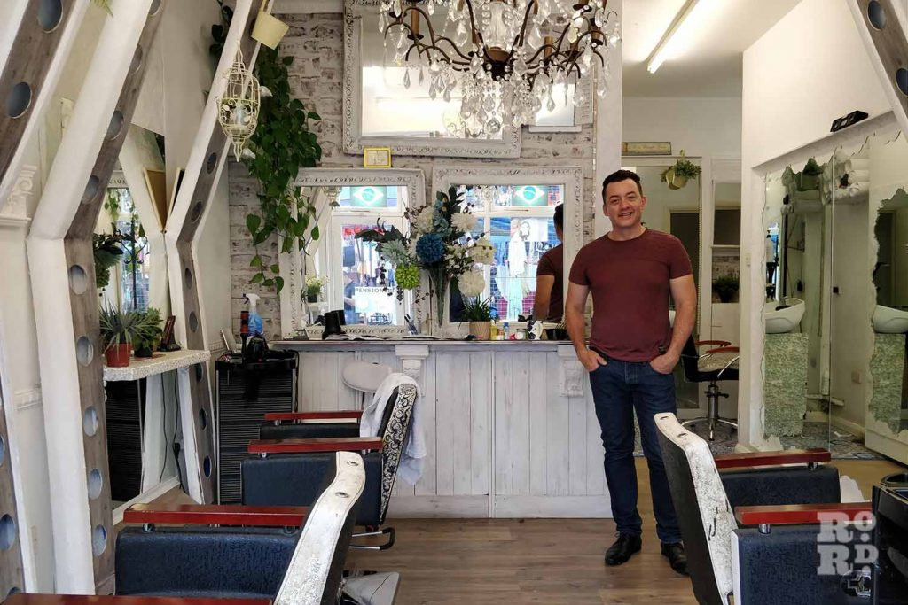 Owner standing inside Creations hairdressing salon, Roman Road, Bow