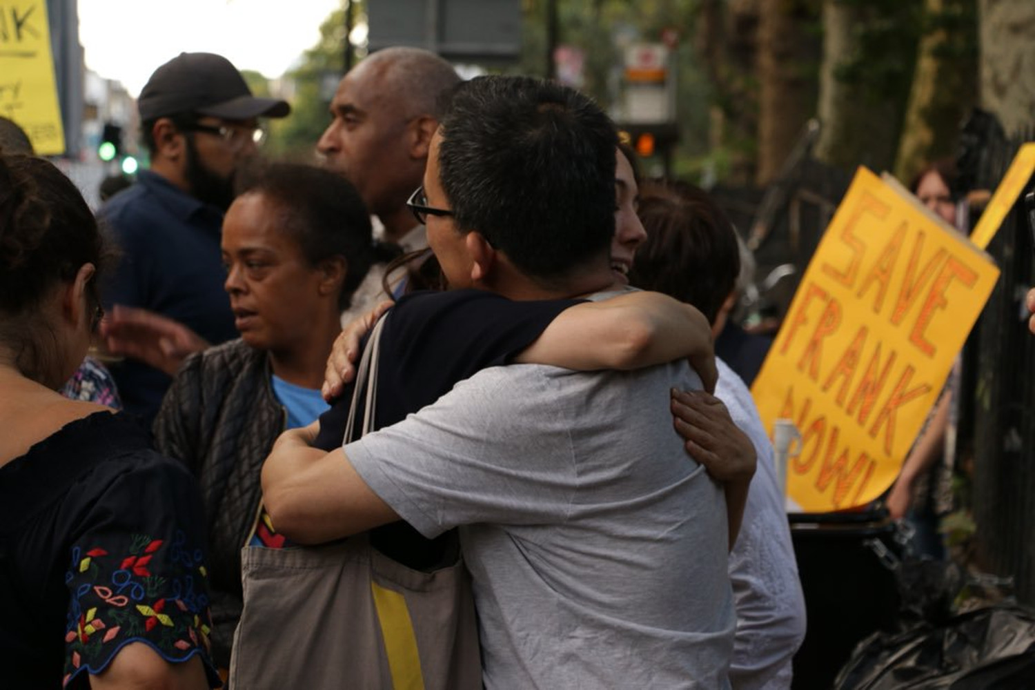 Frank Wang hugging a fellow protester at a demonstration in Bethnal Green