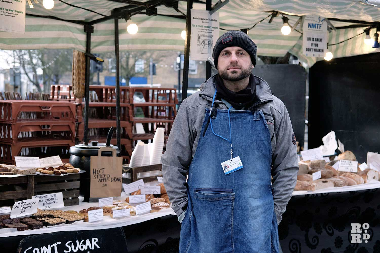 Enzo standing in front of his Saint Sugar of London stall in Roman Road
