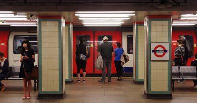 people wait on mile end tube platform for a train