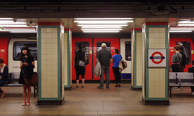 people wait on mile end tube platform for a train
