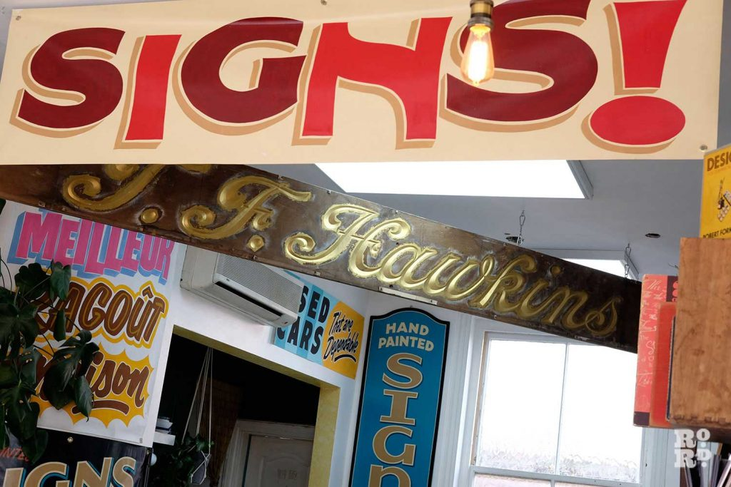 An old toy shop sign hanging from the ceiling in Luminor Sign Co