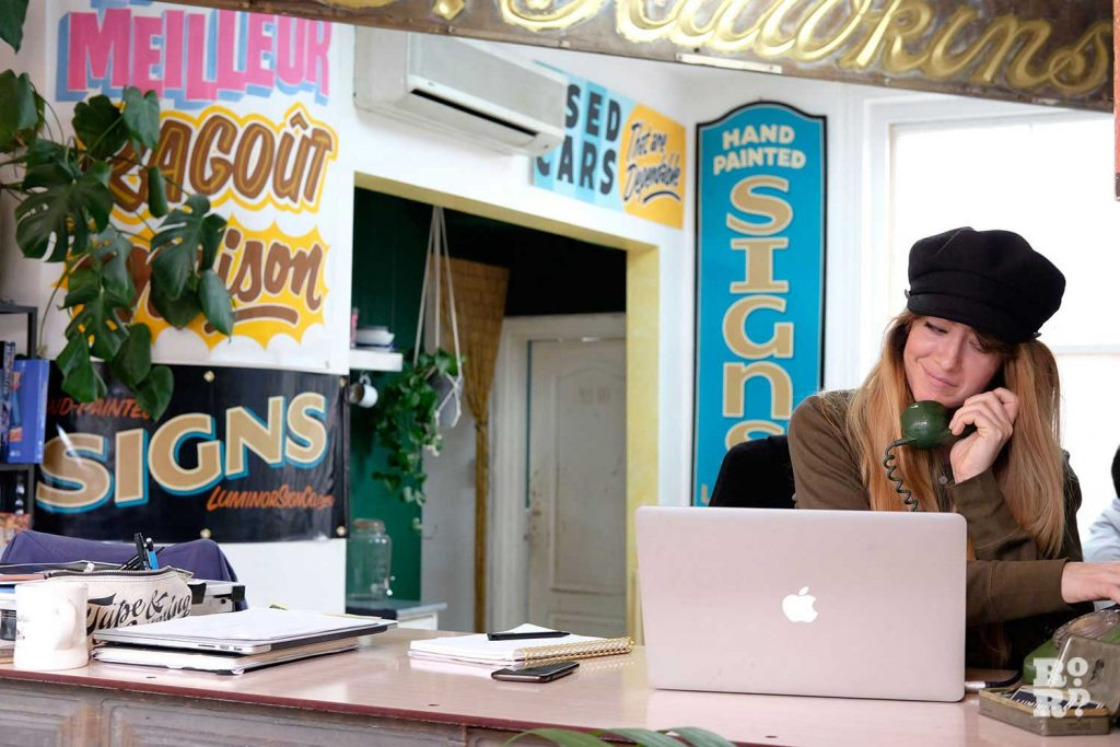 Studio manager Louise Anscomb takes a call at Luminor Sign Co