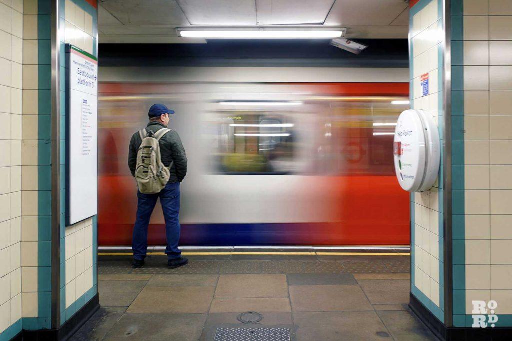 man standing on mile end tube station platform
