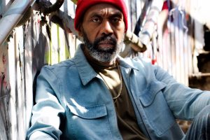 actor Lenny Henry as King Hedley sits on steps