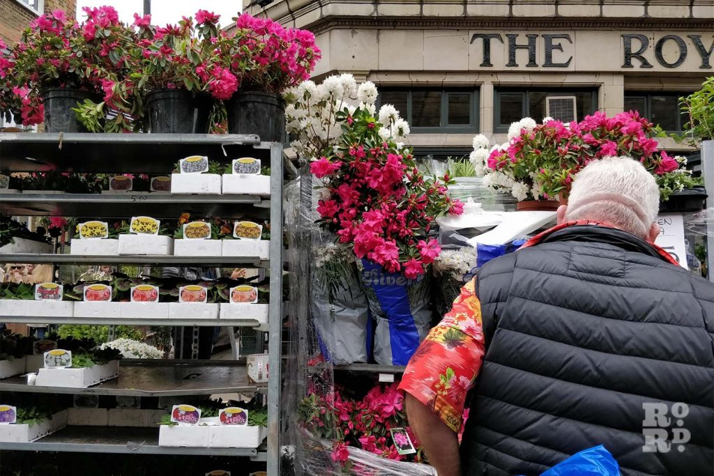 A vendor at Colombia Road Flower Market in front of a pub, East London
