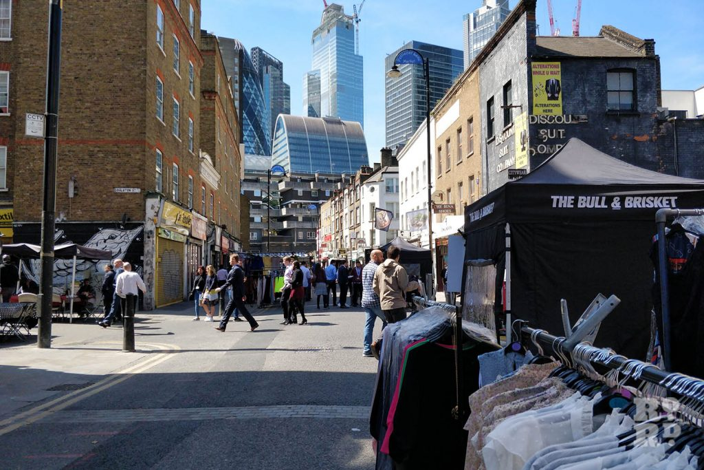 Petticoat Lane Market in East London with City of London skyscrapers behind