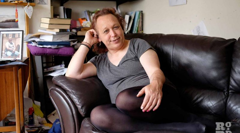 Daniella, trans woman living in Tower Hamlets, sitting on her sofa