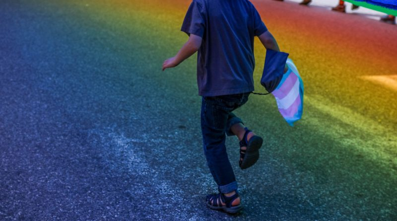 Child runs through LGBT rainbow street holding a transgender flag