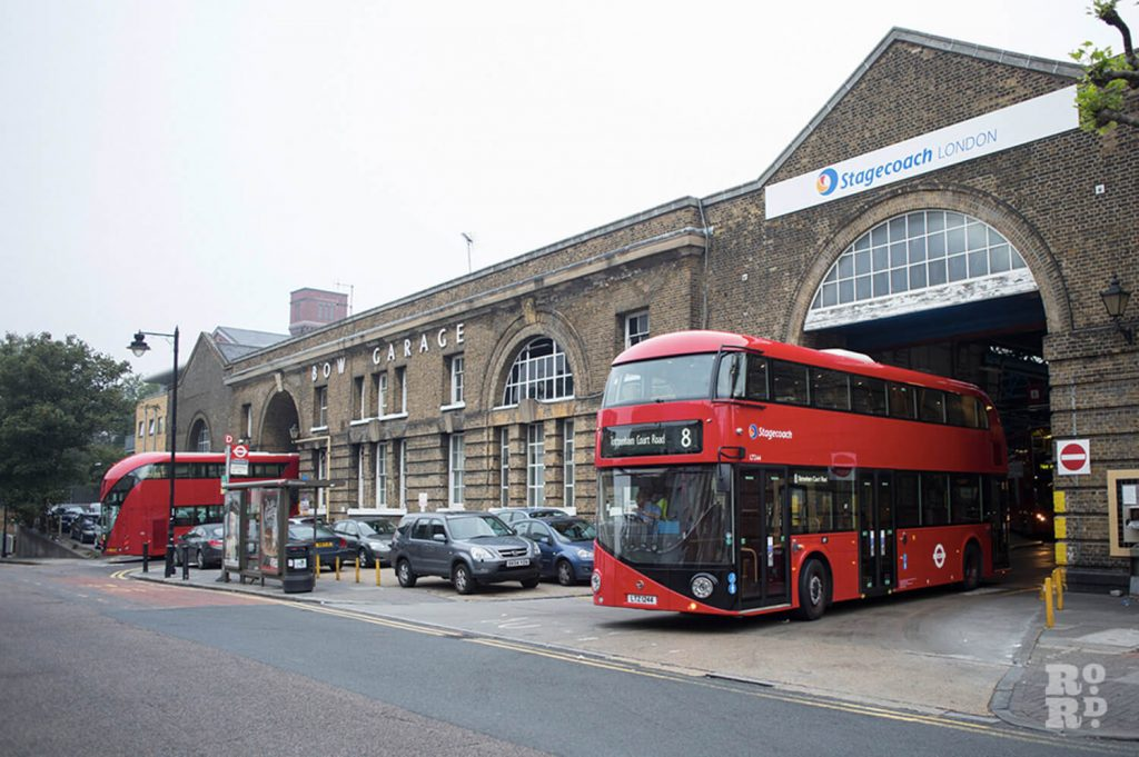 Red double decker no 8 Routemaster London bus exiting Bow Garage in East London