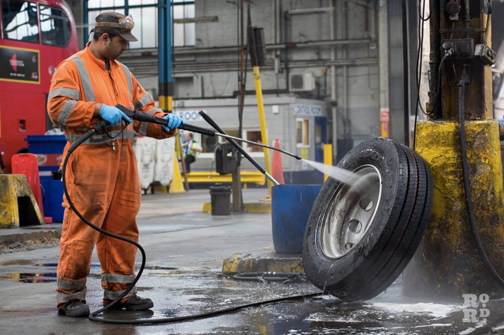 Man in orange overalls and blue clothes using a jet-spray to clean hubs on bus wheels