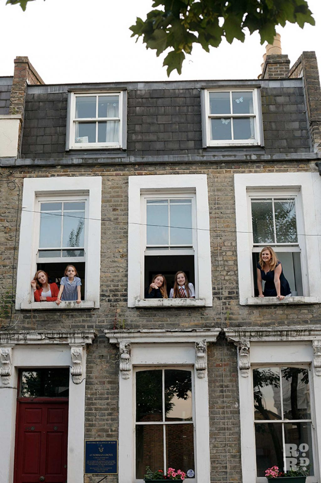 Claire Davis and her children standing at the windows of their Bow home