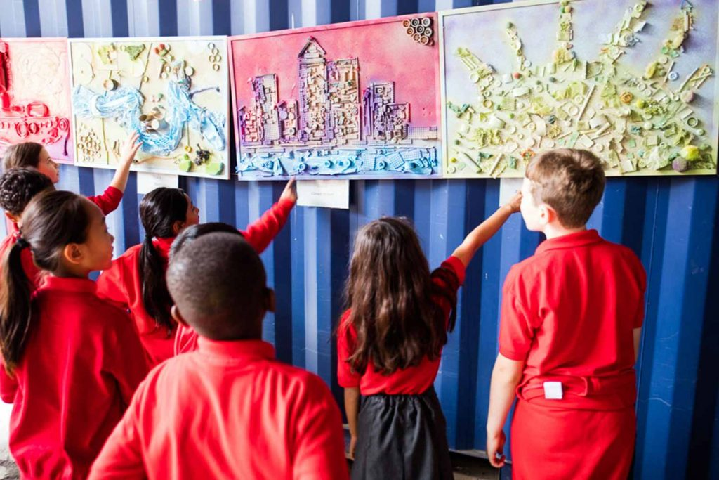Children viewing other students' drawings at Faraday Prep School