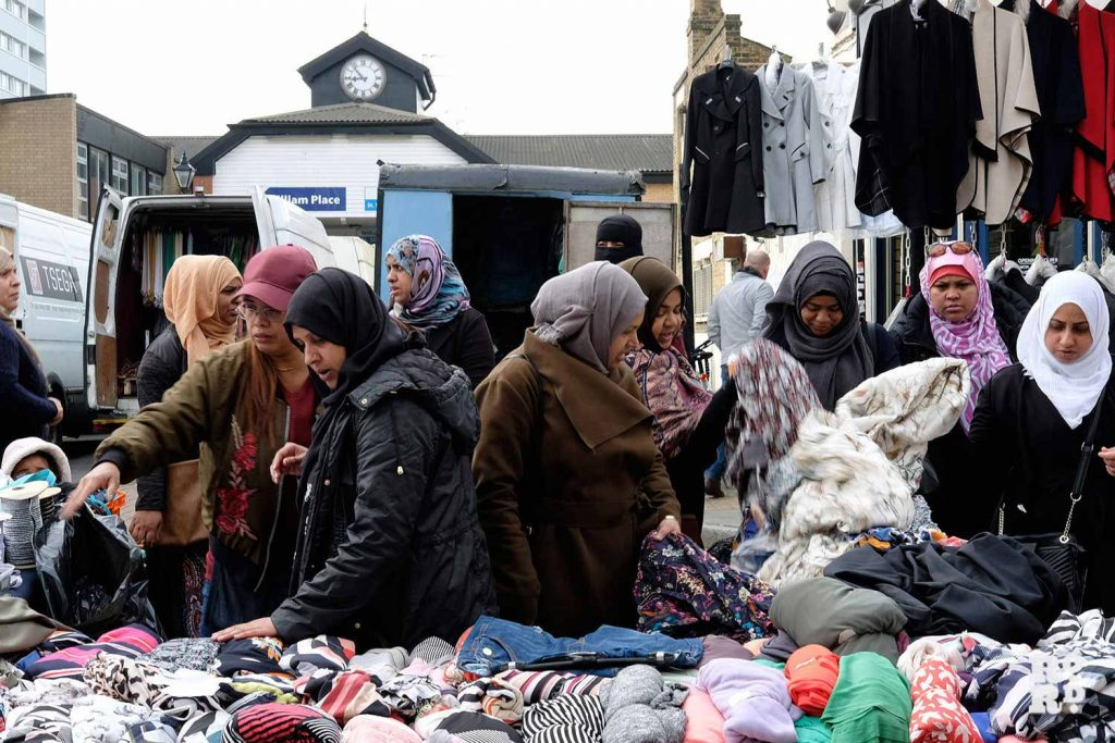 Girls shopping for clothes outside Lucy B's furniture stall on Roman Road Market