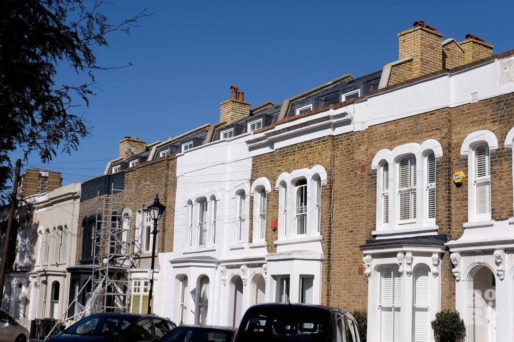 Mansard roofs peeking above residential terraces in Bow