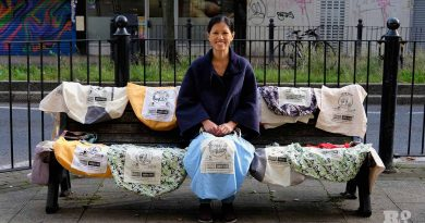 Linda Tai sits with the Roman Road borrow-a-bag tote bags