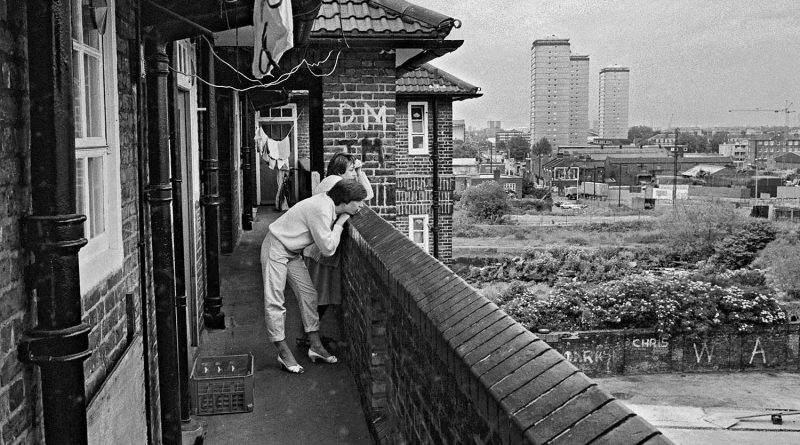 Women staying on the balcony looking out to East London, Isle of Dogs