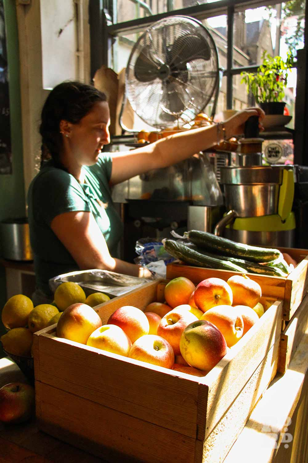 Gallery Cafe staff using juicer with apples and lemons in crates