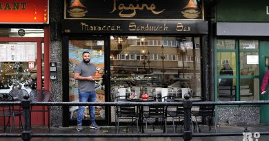 Owner holding tagine dish outside Tagine Moroccan sandwich bar, Globe Town, East London