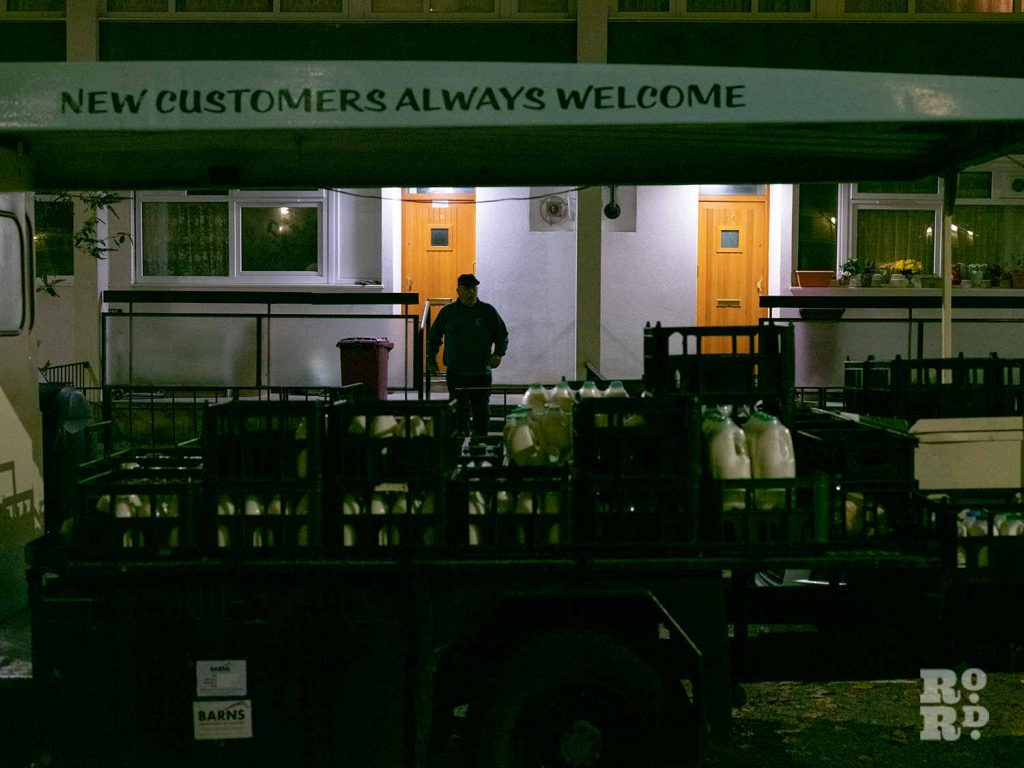 Milk delivery to doorstep by local milkman behind milk float in Bow