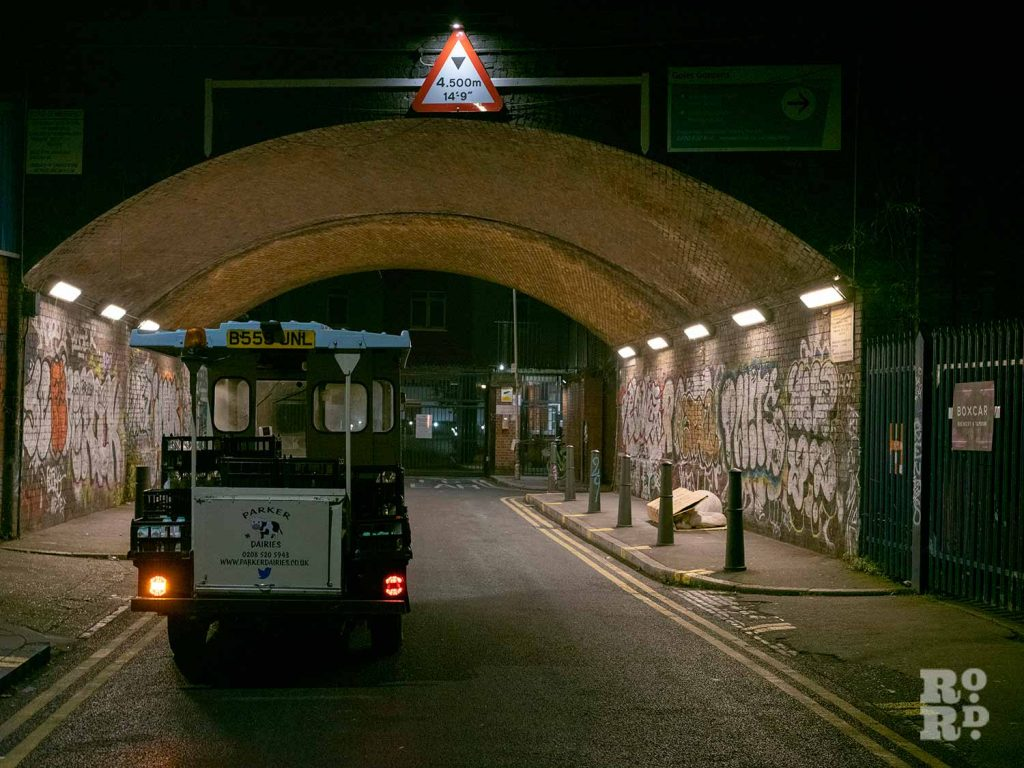 Milk float parked in railway underpass in East London