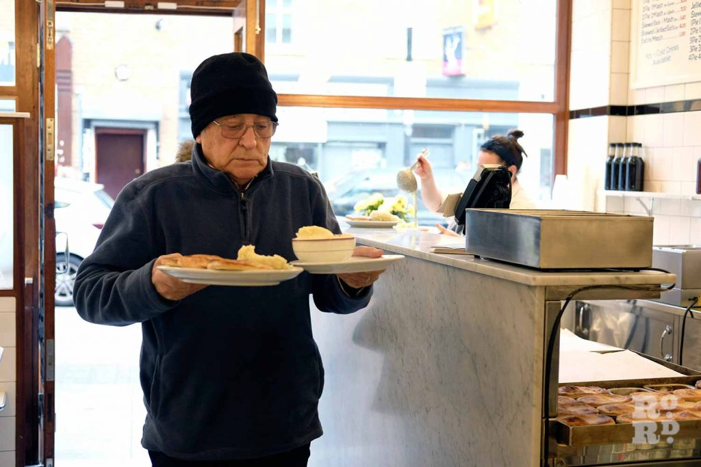 G.Kelly pie and mash Roman Road customer carrying plate of pie and mash