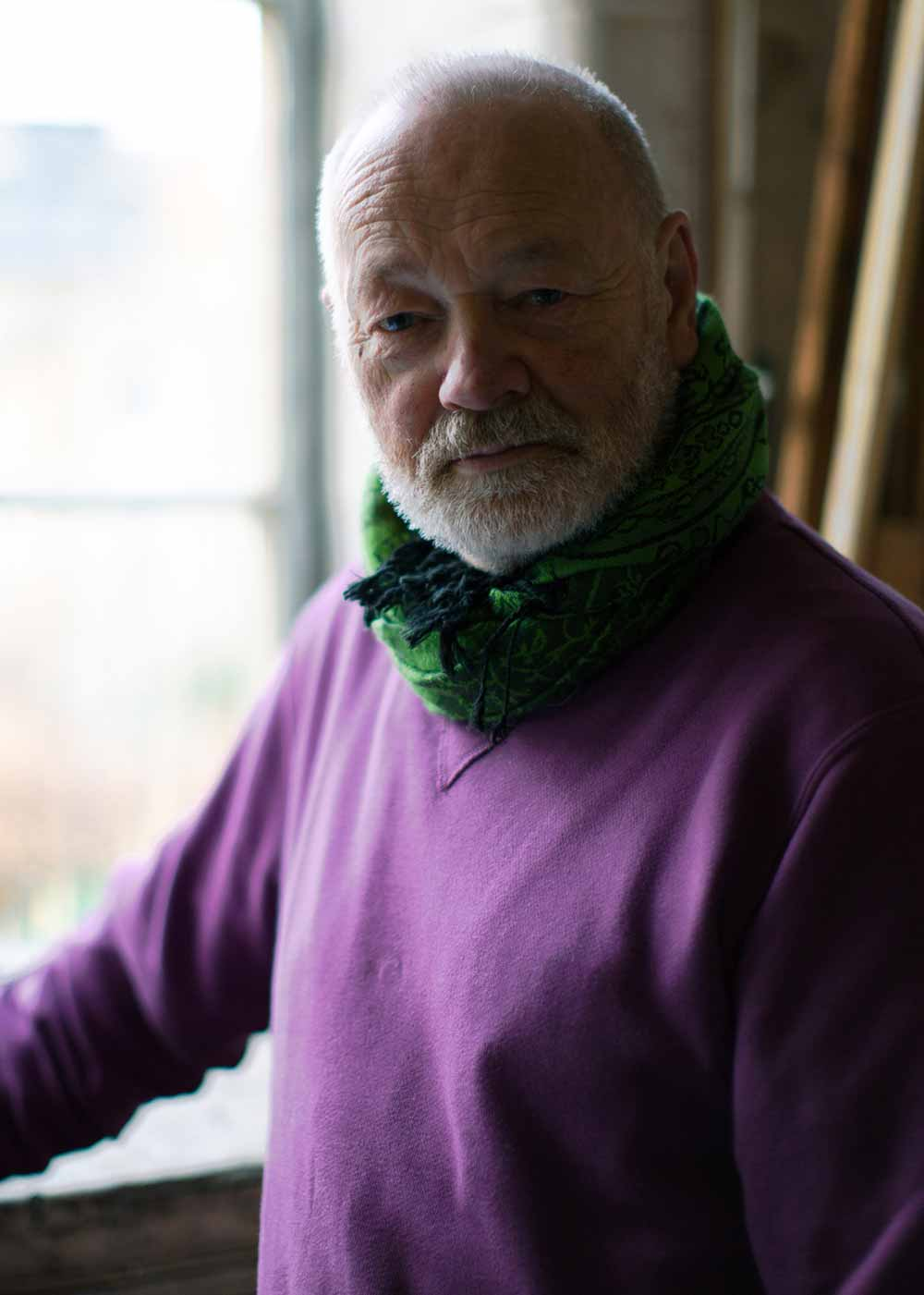 Portait of artist Jon George, wearing purple jumper