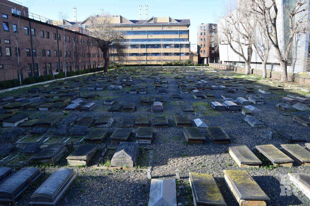 Many horizontal gravestones with Queen Mary university buildings in the background at Novo Jewish Cemetery, Mile End, London.