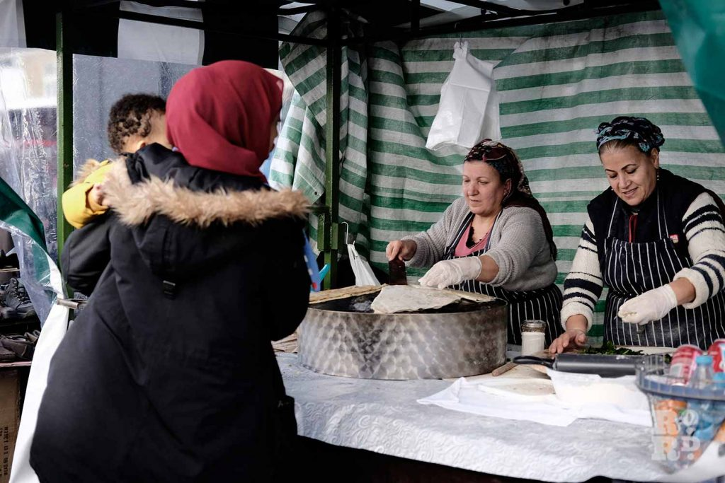 Women making Turkish gozleme at hot food stall at Roman Road Market, East London