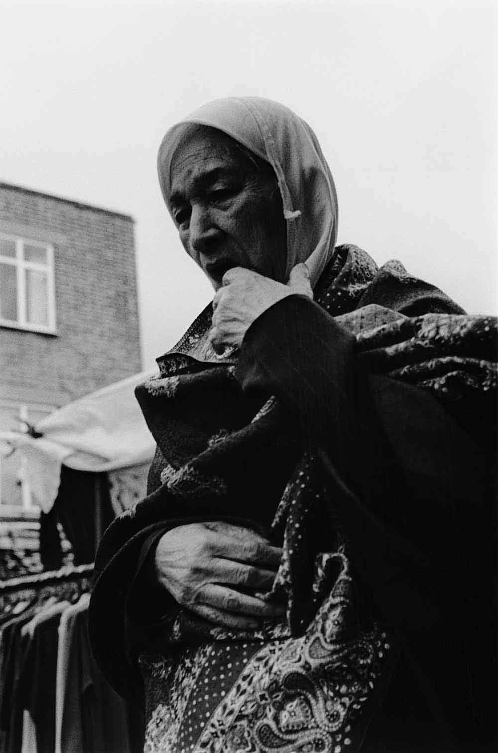 Asian woman in a headscarf, part of a series of photographs by Stephie Devred that captures the unique spirit of the East London street market, Roman Road Market.