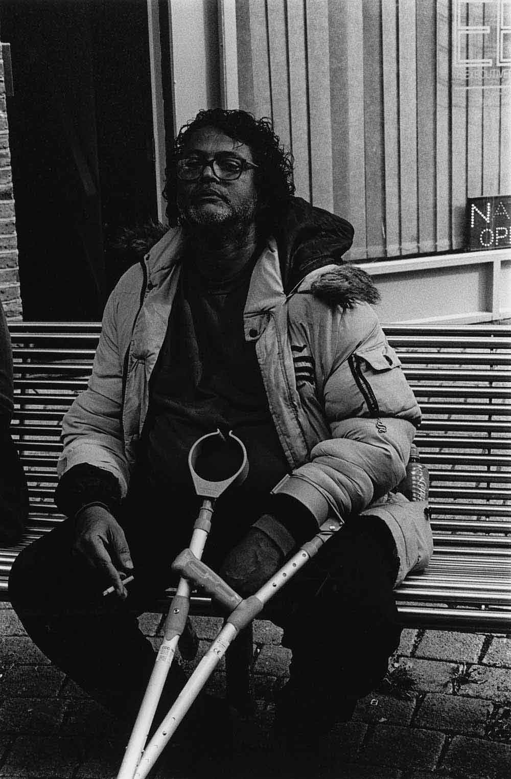Man with crutches smoking a cigarette on a street bench, part of a series of photographs by Stephie Devred that captures the unique spirit of the East London street market, Roman Road Market.