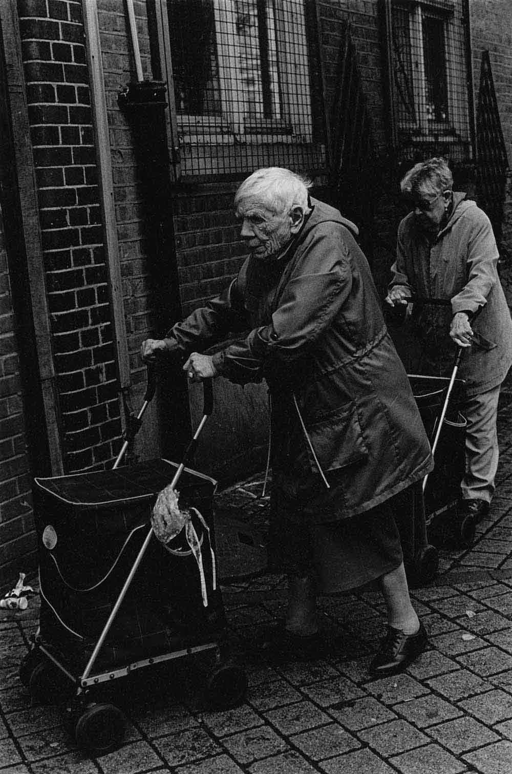 Two elderly women pushing shopping trolleys, part of a series of photographs by Stephie Devred that captures the unique spirit of the East London street market, Roman Road Market.