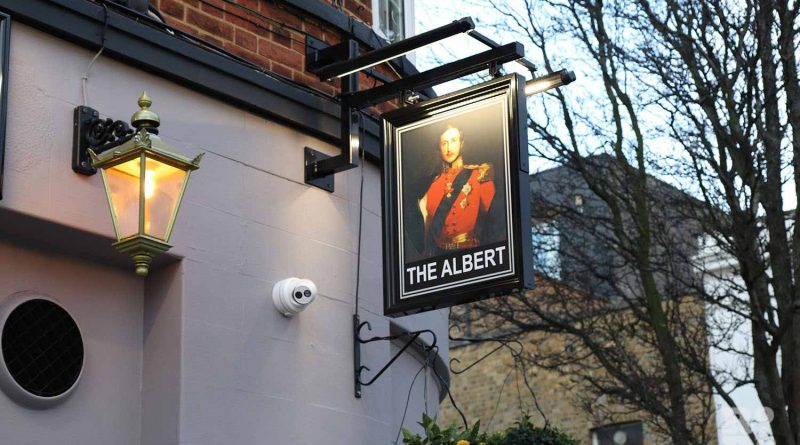 The new pub sign hanging above The Albert at the entrance of Roman Road Market, Bow, East London