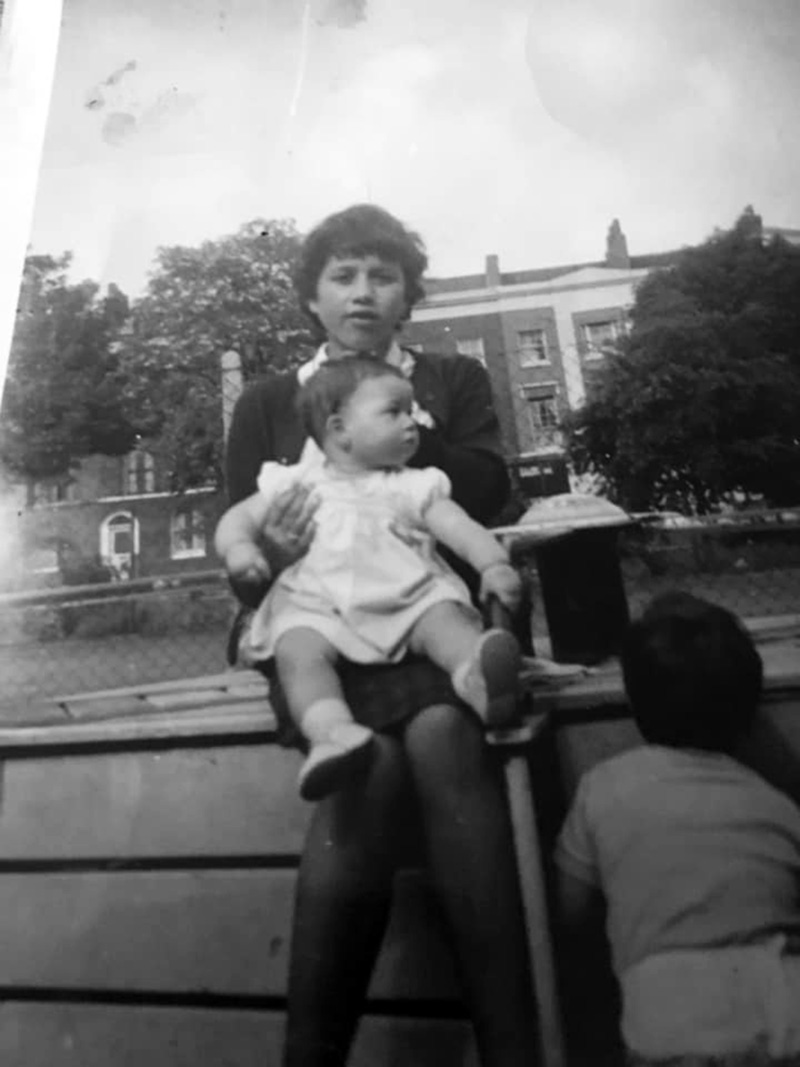 Archive image from 1964 of girl holding baby on lap in Tredegar Square, Mile End, London