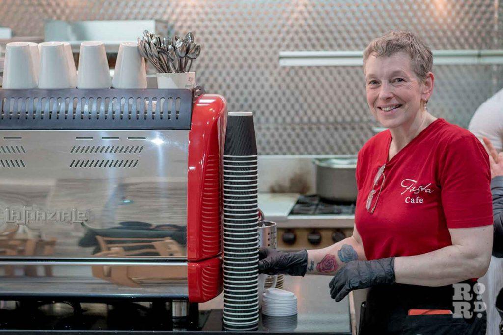 Waitress next to coffee machine, Fiesta Cafe on Roman Road, East London