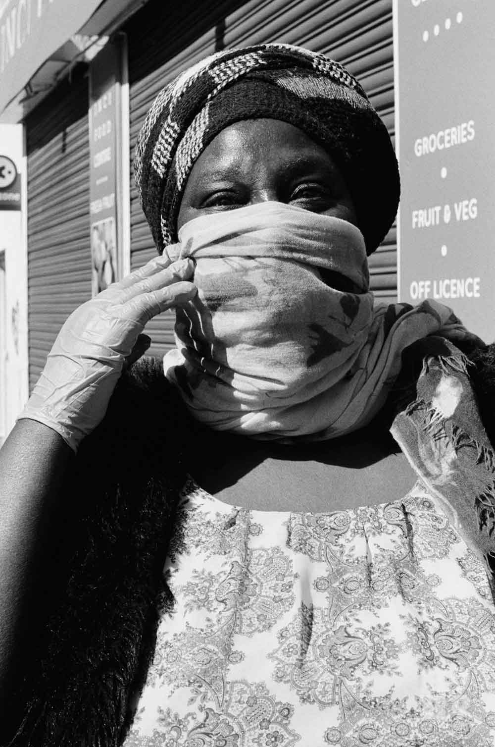 Black and white image of woman wearing a scarf around her mouth during lockdown