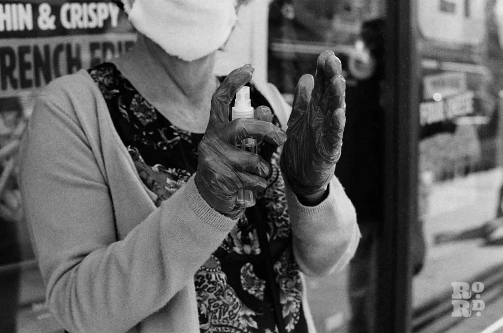 Woman wearing face masks and gloves sprays hand sanitiser onto her gloves