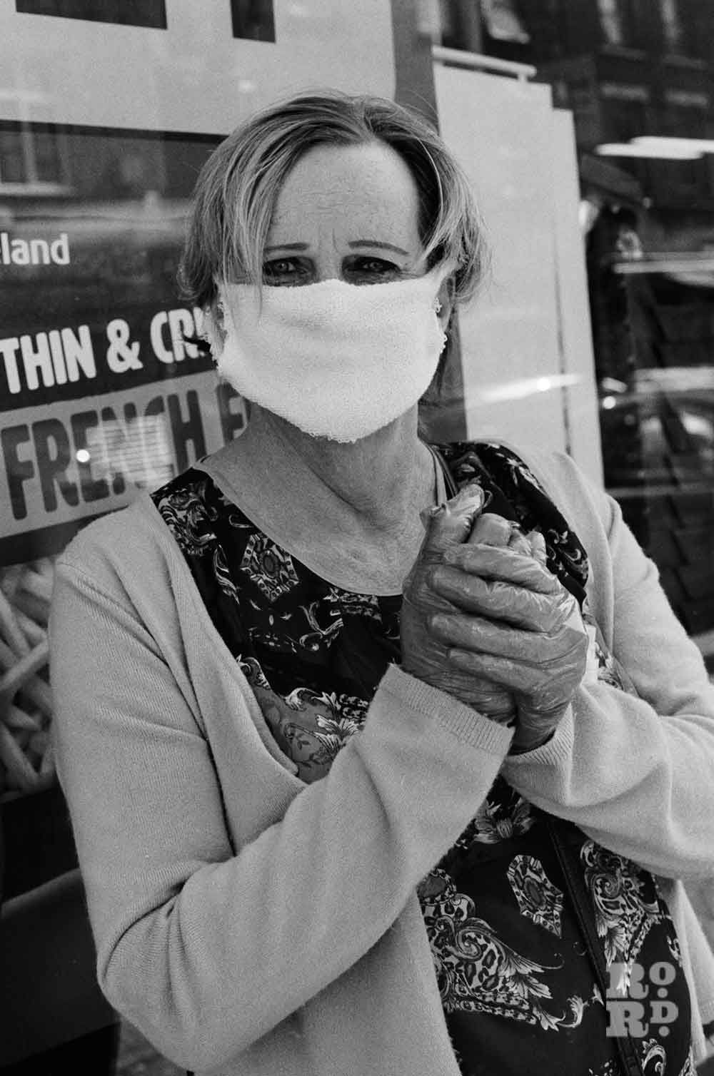 Black and white image of a woman looking into the camera wearing homemade mask and disposable gloves while queuing for Iceland