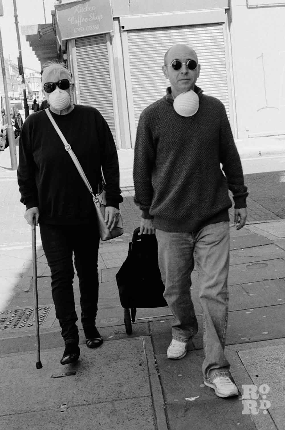 Black and white portrait of a woman and a man in masks walking down Roman Road