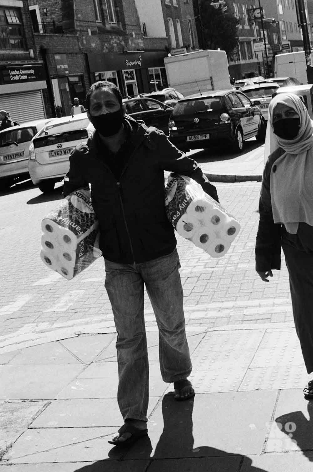 Woman and man in masks carry toilet paper down Roman Road in lockdown