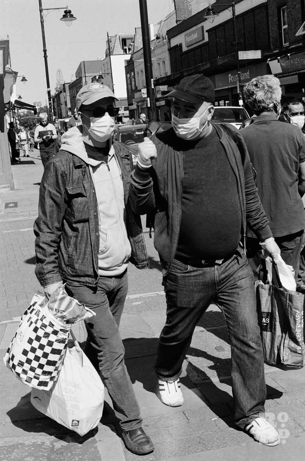 Black and white image of two men in masks carry shopping down Roman Road