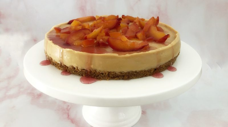 Photo of a white chocolate and biscoff cheesecake topped with a nectarine fruit compote and syrup on a white circular cake stand