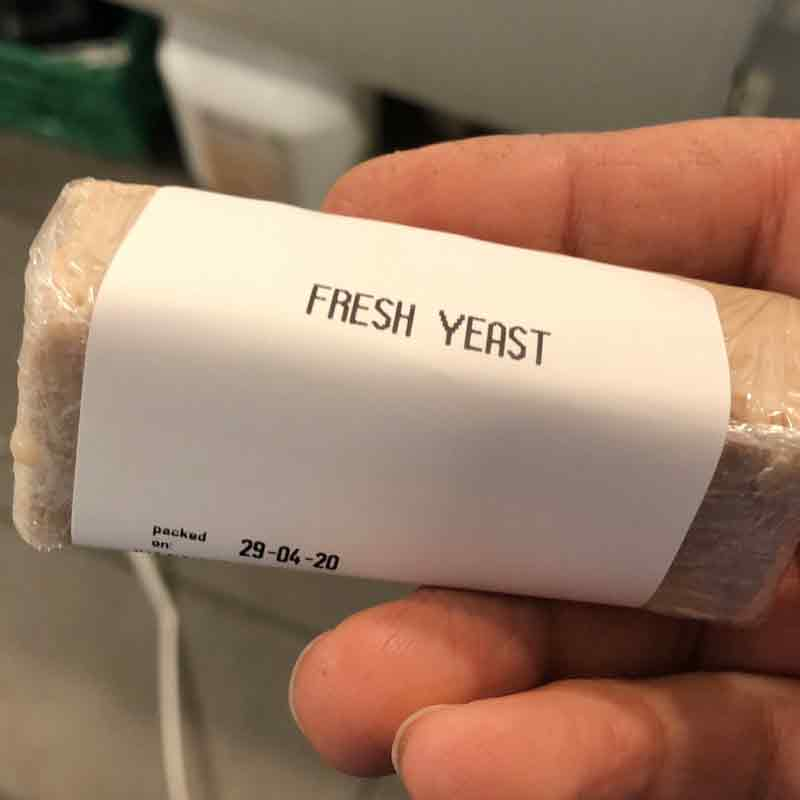 Someone holding a packet of fresh yeast